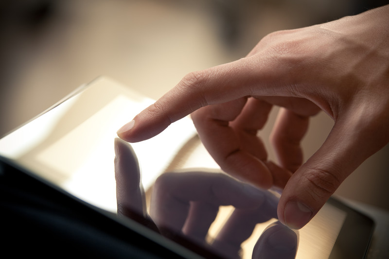 woman's hand navigating tablet device