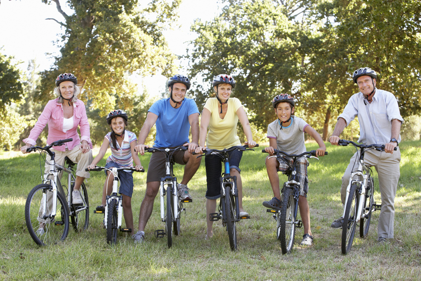 Three Generation Family On Cycle Ride In Countryside Smiling At Camera.
