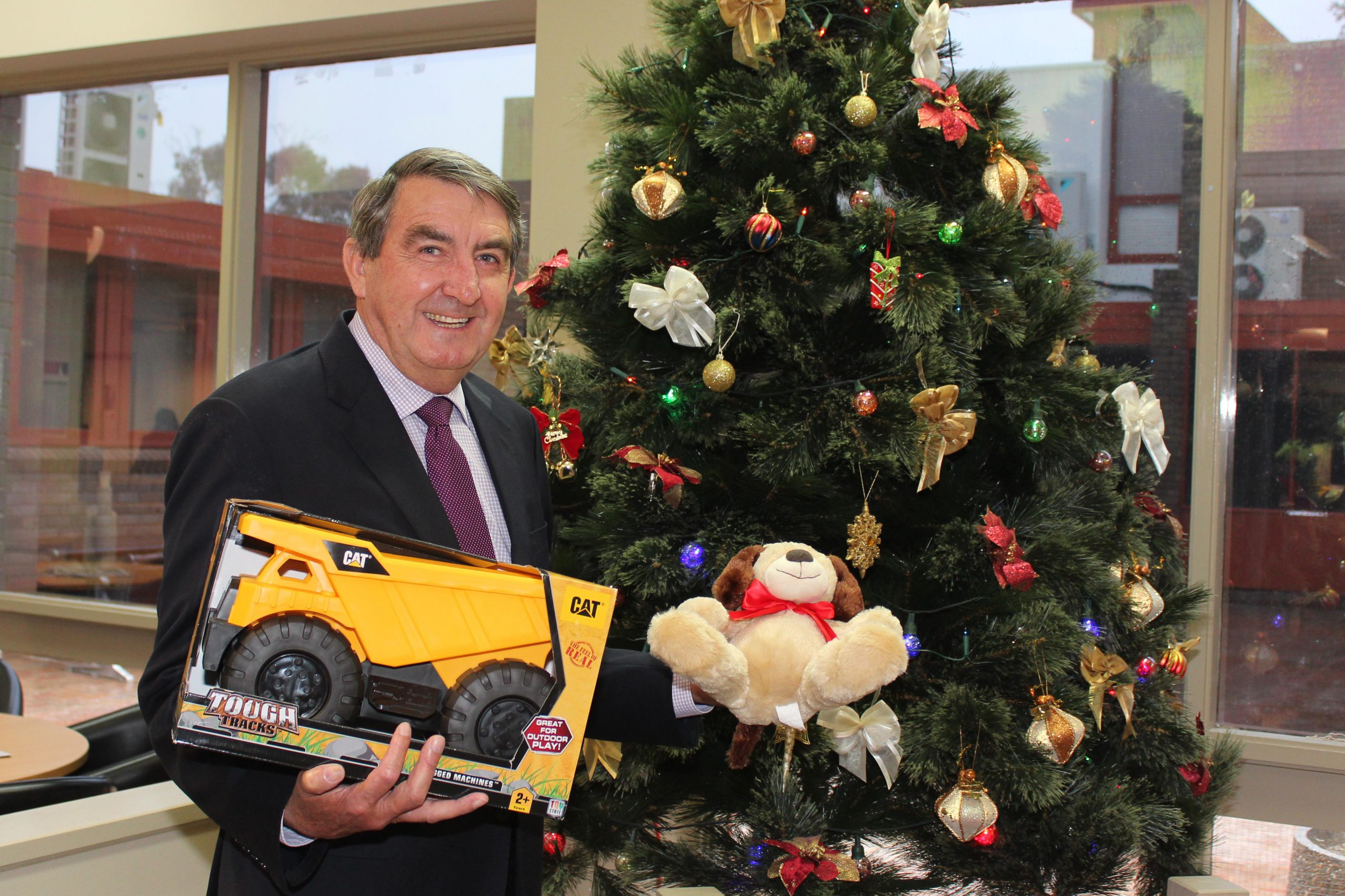 Mayor Duncan Gair holding gift in front of 2018 Christmas Giving Tree
