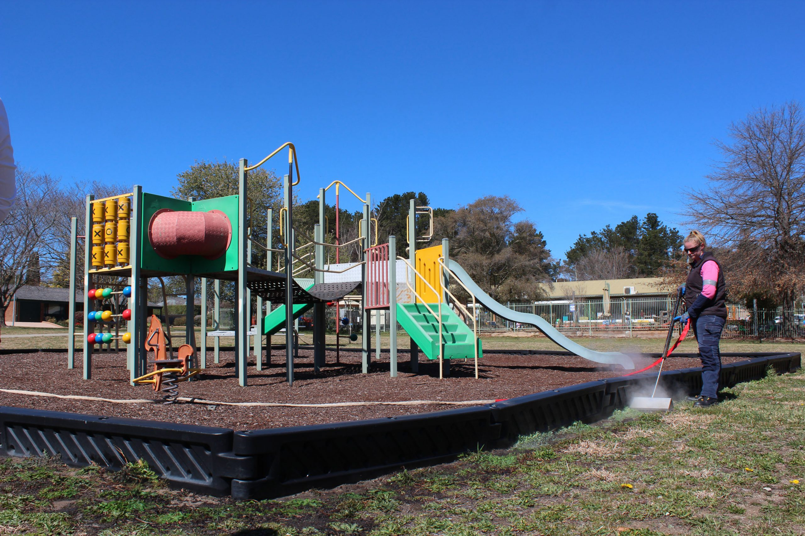 Playground equipment with person demonstrating weed control method