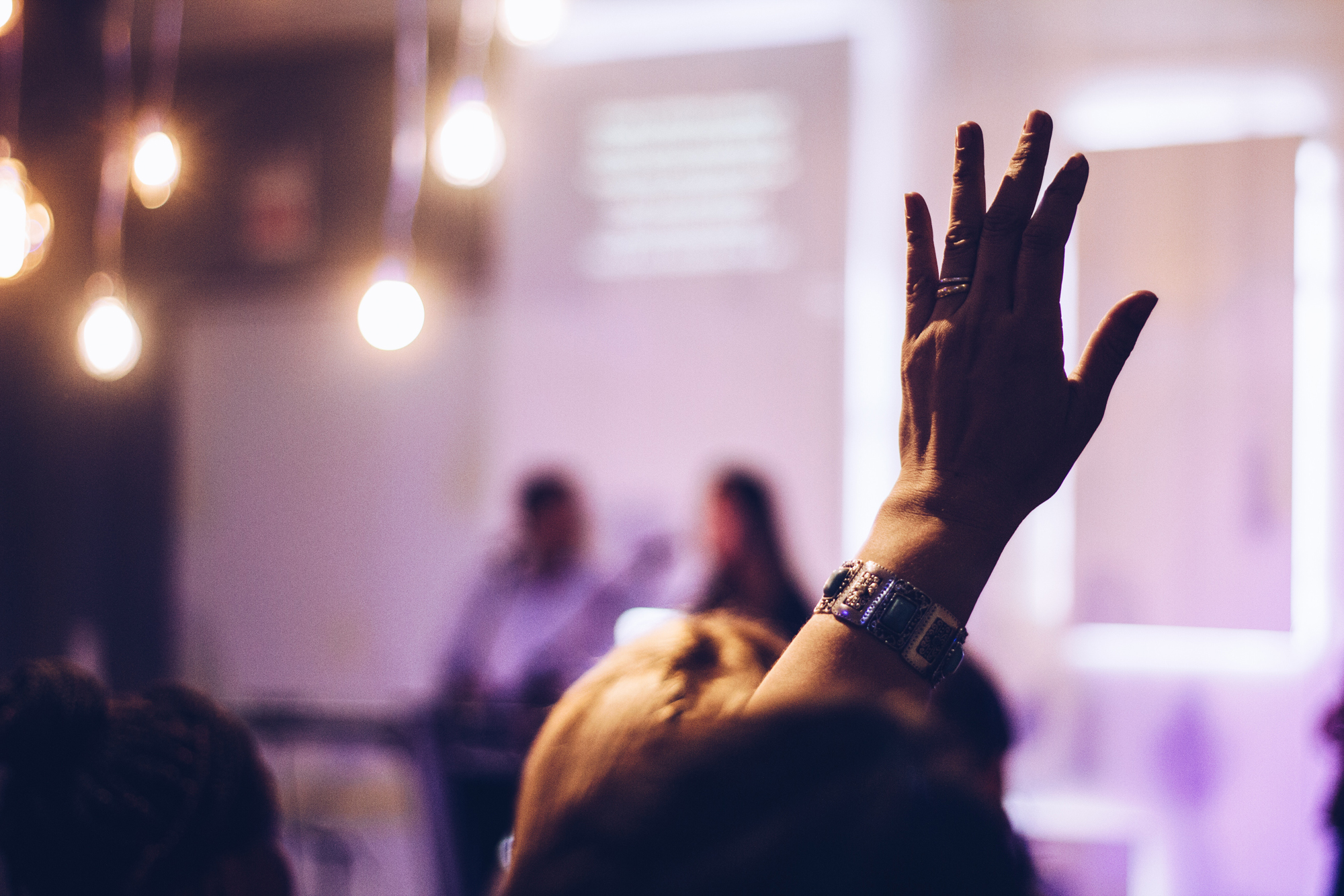 person raising hand in community information session