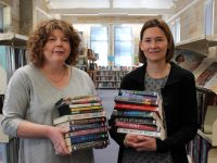 Two female librarians holding stacks of books inside library