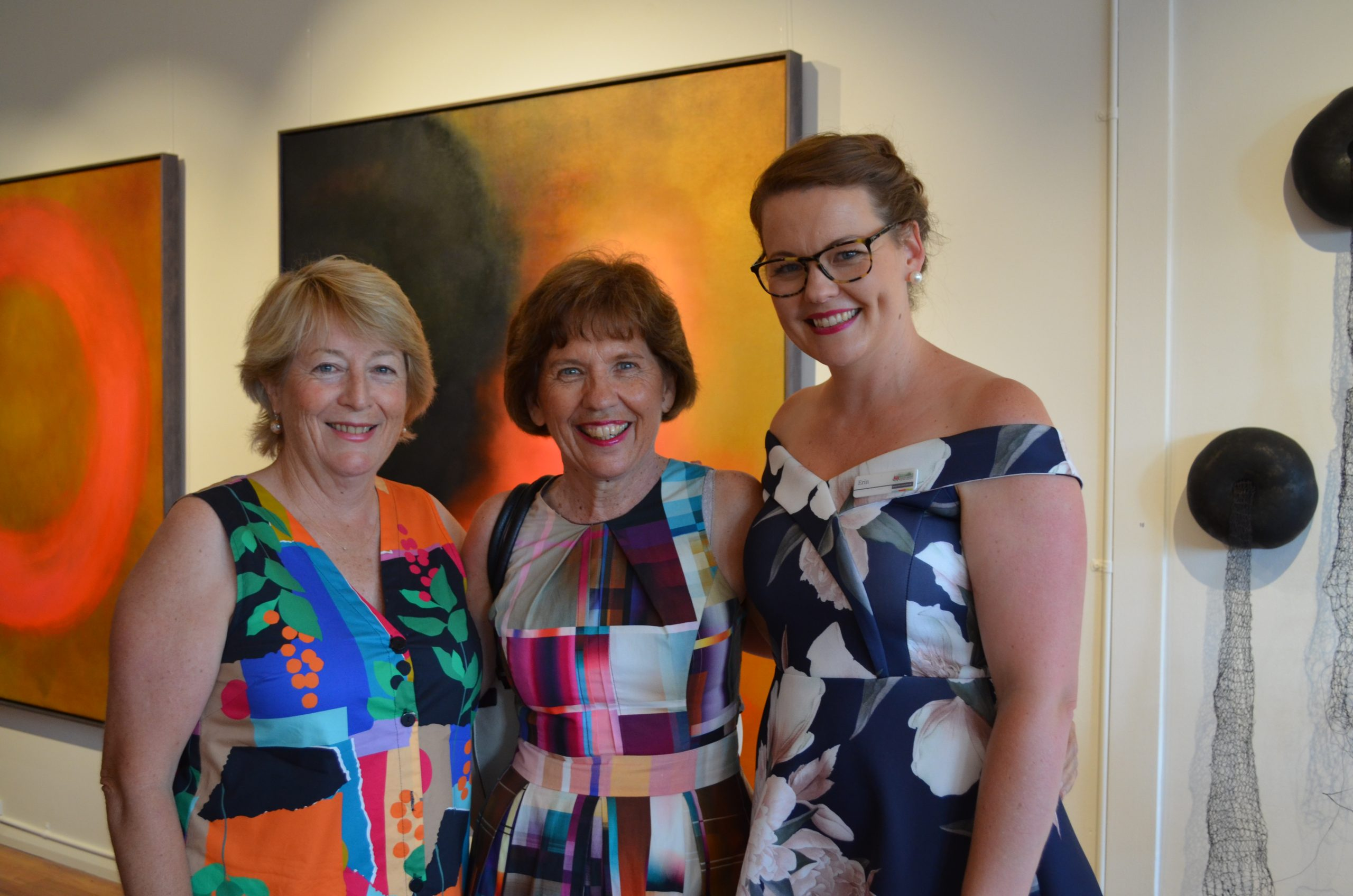 Three ladies smiling, standing in front of colourful abstract artwork