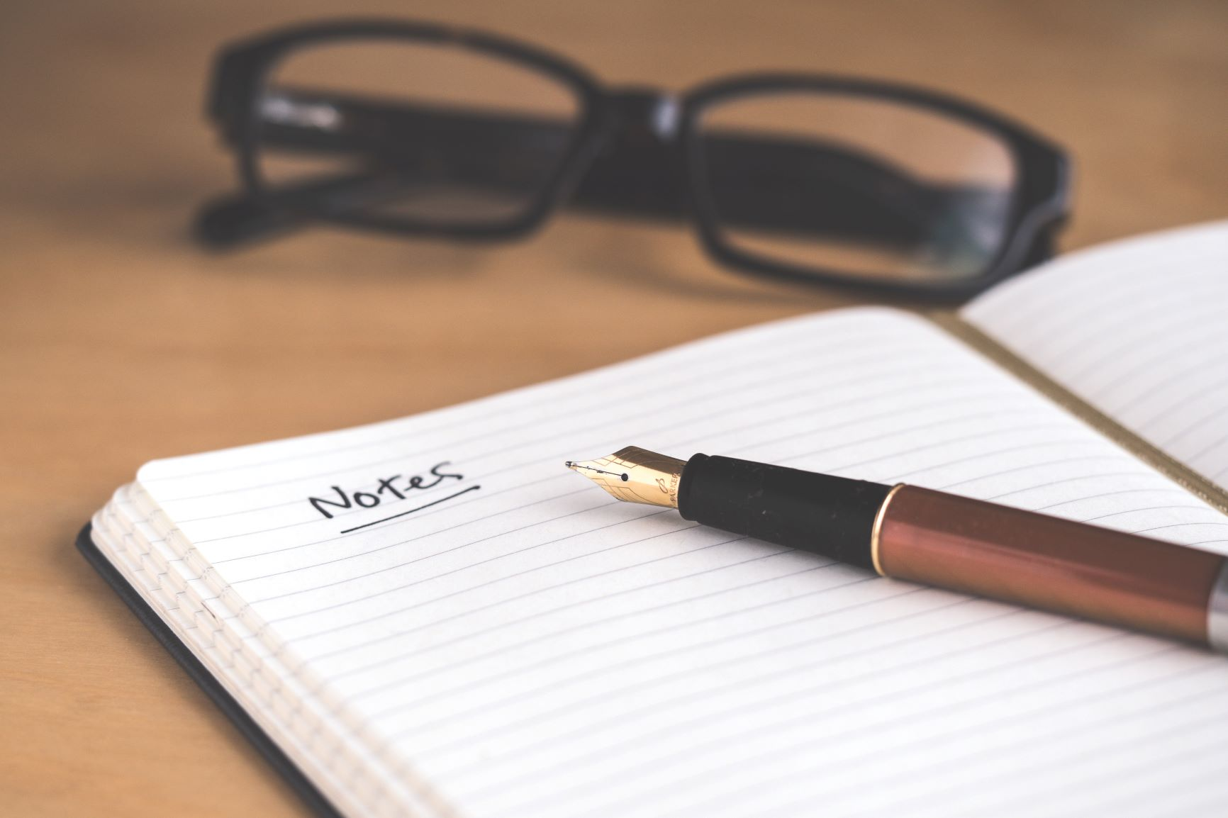 Glasses and open notepad and pen sitting on desk