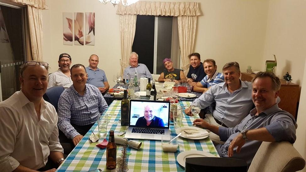 Group of men sitting around table socialising