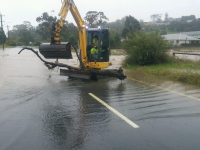 Machinery scooping up flood water