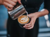 person pouring milk froth into coffee