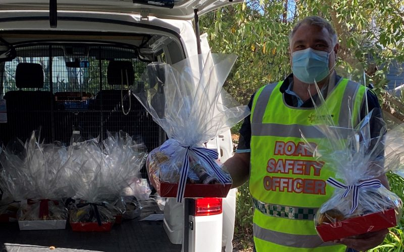 Hampers being packed into boot by man in hi vis vest
