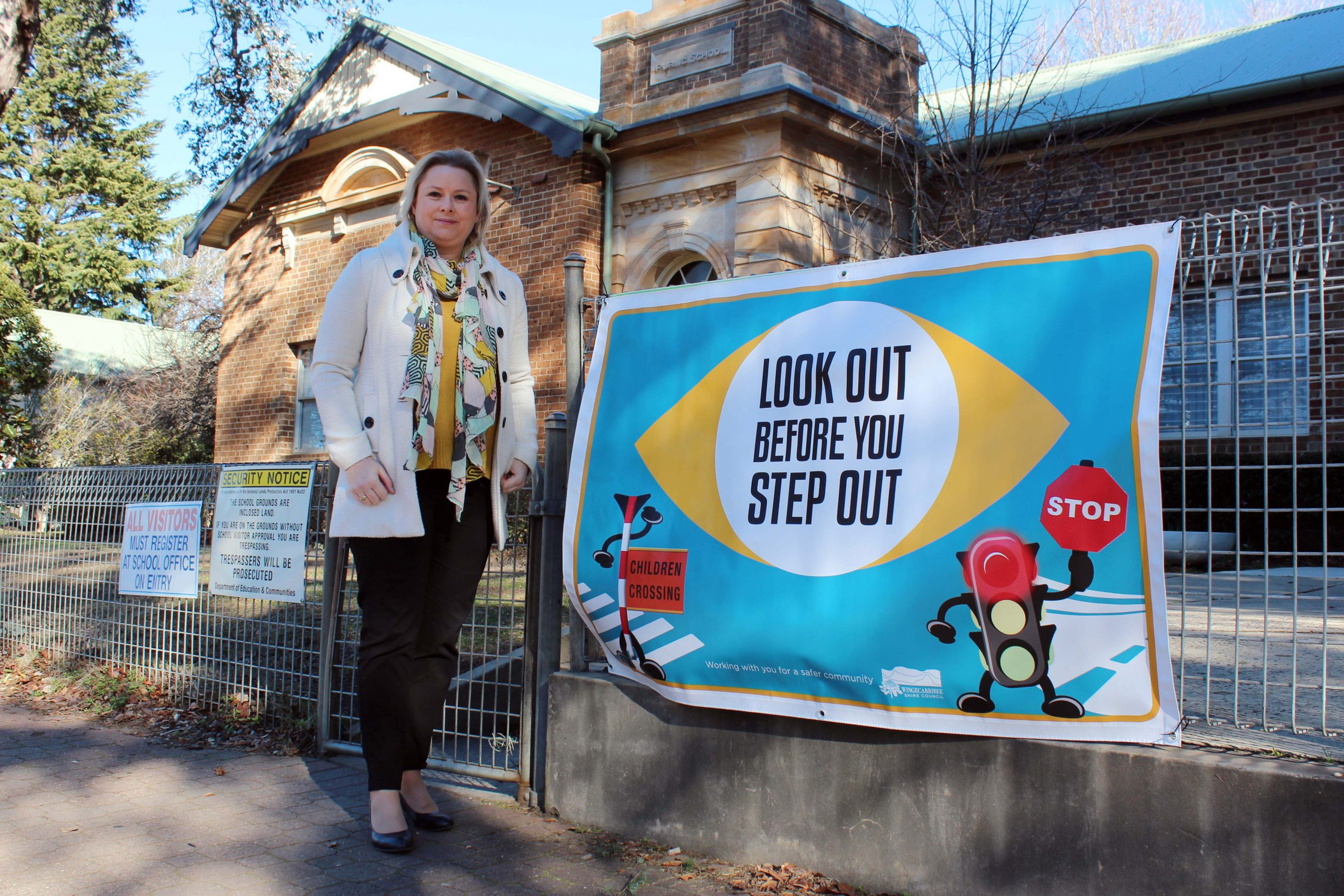 Road Safety Officer, Melanie Lausz, with the custom 'Look out before you step out' banner at Bowral Public School