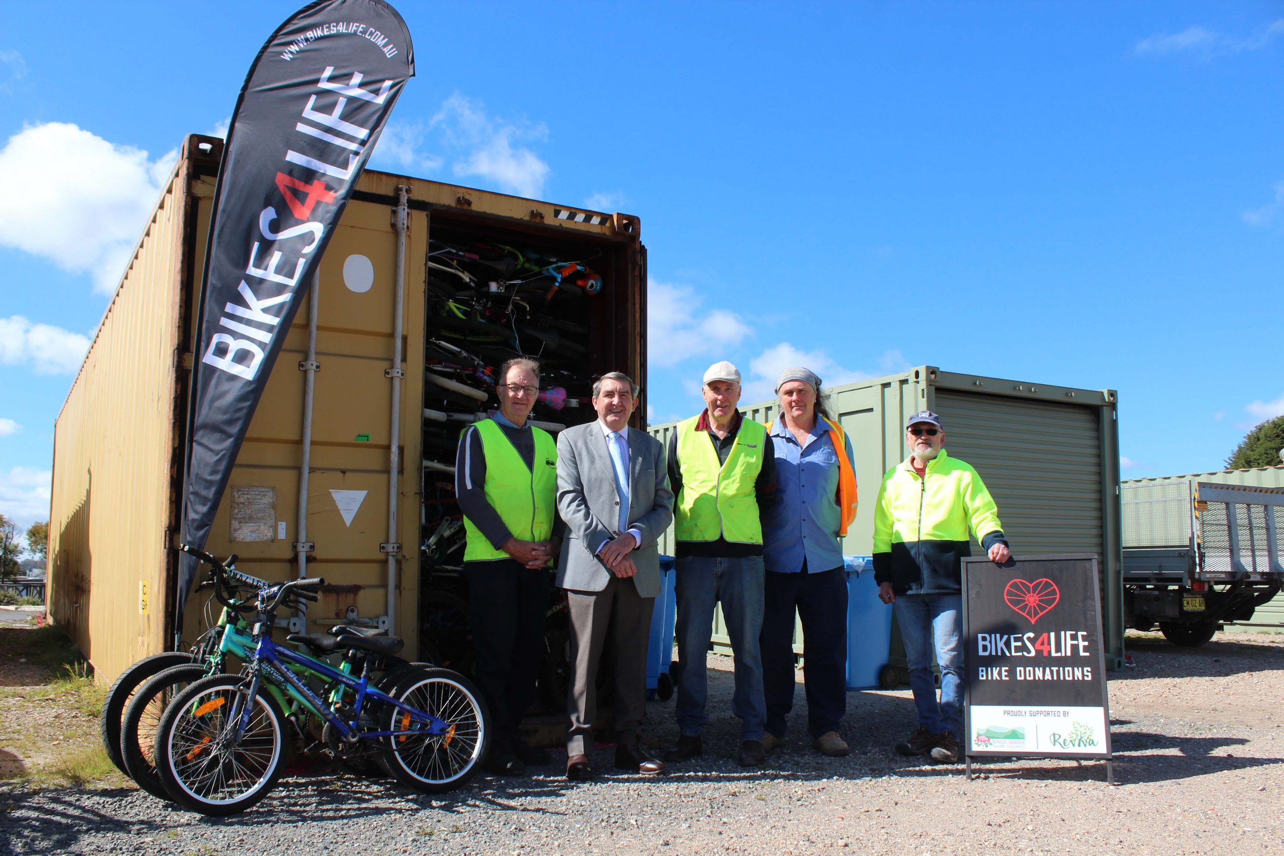 People pose in front of shipping container filled with bikes