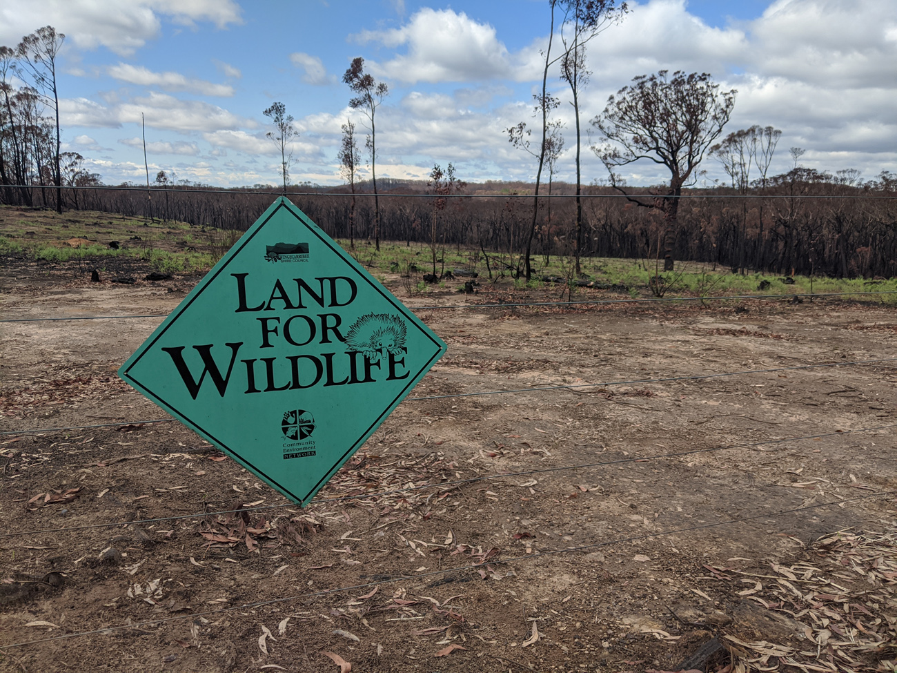 Land for Wildlife sign and burnt landscape