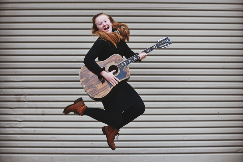 young girl with guitar jumping with joy