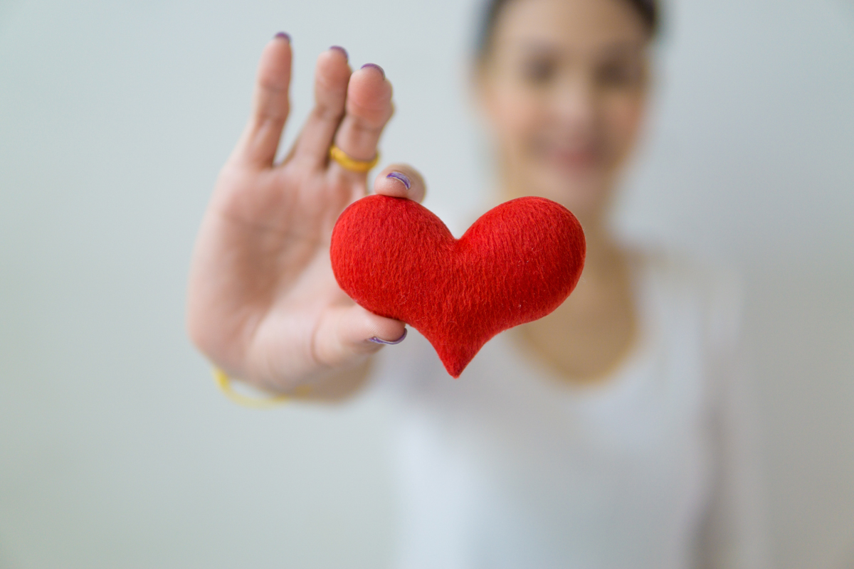 Close up of small red felt heart, held by woman