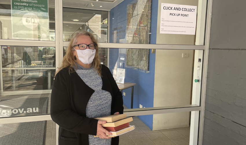 Librarian in face mask standing outside library, ready to hand over books to customer